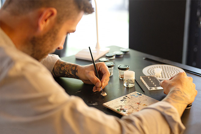 Ocularist hand painting a prosthetic eye